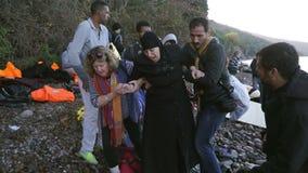 LESVOS, GRÉCIA - 5 DE NOVEMBRO DE 2015: Os voluntários ajudam a mulher do refugiado a ir na costa filme