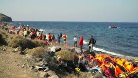 LESVOS, GRÉCIA - 5 DE NOVEMBRO DE 2015: Povos corridos ao barco de aproximação com refugiados