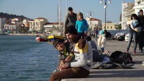 LESVOS, GRÉCIA - 5 DE NOVEMBRO DE 2015: Refugiados no cais de Mytilene que espera a balsa filme