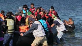 LESVOS, GRECIA - 2 DE NOVIEMBRE DE 2015: Bote de goma de la licencia de los refugiados cerca de la orilla metrajes