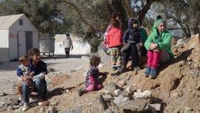 LESVOS, GRECIA - 5 DE NOVIEMBRE DE 2015: Gente en el campamento de refugiados Las mujeres con los niños se sientan en la tierra almacen de metraje de vídeo