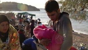 LESVOS, GRECIA - 5 DE NOVIEMBRE DE 2015: Hombre joven con un bebé en la orilla metrajes