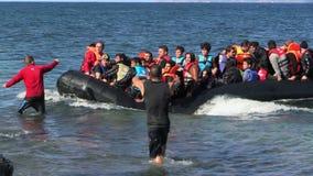LESVOS, GRECIA - 2 DE NOVIEMBRE DE 2015: Los refugiados en un bote de goma nadan para apuntalar de Turquía almacen de video