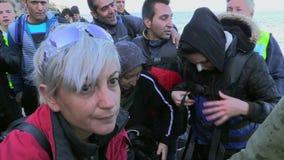 LESVOS, GRECIA - 2 DE NOVIEMBRE DE 2015: Refugiados en la orilla en un estado del choque después de cruzar el mar almacen de video