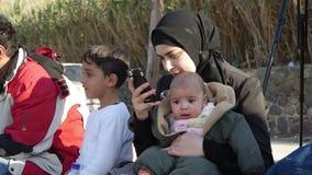 LESVOS, GRECIA - 5 DE NOVIEMBRE DE 2015: Refugiados en la orilla Mujer árabe con el bebé almacen de video