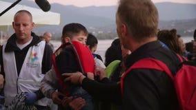 LESVOS, GRECIA - 5 DE NOVIEMBRE DE 2015: Refugiados que fueron rescatados en el mar Ayuda en la orilla almacen de video
