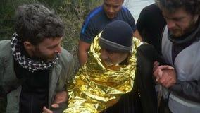 LESVOS, GRECIA - 5 NOVEMBRE 2015: I volontari aiutano il rifugiato anziano a andare sulla riva stock footage