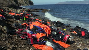 Free LESVOS, GREECE - NOV 2, 2015: Abandoned By The Refugees Belongings And Life Jackets On The Rocky Shore. Royalty Free Stock Photos - 80180018