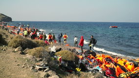LESVOS, GREECE - NOV 5, 2015: People run to the approaching boat with refugees. Volunteers, Red Cross, Journalists and local people