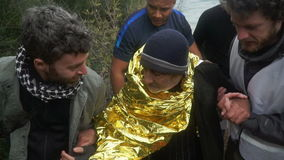 LESVOS, GREECE - NOV 5, 2015: Volunteers help old refugee to go on shore.