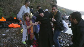 LESVOS, GREECE - NOV 5, 2015: Volunteers help refugee woman to go on shore.