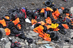 LESVOS, GREECE OCTOBER 24, 2015: Lifejackets, rubber rings an pieces of the rubber dinghys discarded on a beach near Molyvos. LESVOS, GREECE OCTOBER 24, 2015 royalty free stock photography