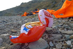 LESVOS, GREECE OCTOBER 24, 2015: Lifejackets, rubber rings an pieces of the rubber dinghys discarded on a beach near Molyvos. Eftalou and Skala Sikaminia royalty free stock photo