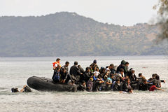 LESVOS, GREECE october 12, 2015: Refugees arriving in Greece in dingy boat from Turkey. These Syrian, Afghanistan and African refugees land their boat at the royalty free stock photos