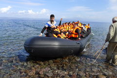LESVOS, GREECE october 12, 2015: Refugees arriving in Greece in dingy boat from Turkey. These Syrian, Afghanistan and African refugees land their boat at the stock images