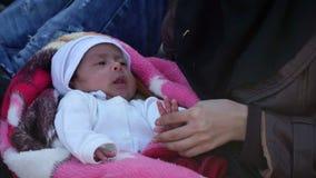 LESVOS GREKLAND - NOVEMBER 5, 2015: Flyktingar på stranden Den arabiska kvinnan med behandla som ett barn