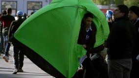 LESVOS GREKLAND - NOVEMBER 5, 2015: Flyktingmannen bär ett tält i vinden i port av Mytilene lager videofilmer