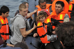 LESVOS, GRIECHENLAND am 20. Oktober 2015: Flüchtlinge, die in Griechenland im schmuddeligen Boot von der Türkei ankommen Lizenzfreie Stockbilder