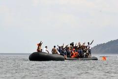 LESVOS, GRIECHENLAND am 12. Oktober 2015: Flüchtlinge, die in Griechenland im schmuddeligen Boot von der Türkei ankommen Lizenzfreie Stockfotos