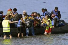 LESVOS, GRIECHENLAND am 12. Oktober 2015: Flüchtlinge, die in Griechenland im schmuddeligen Boot von der Türkei ankommen Stockfoto