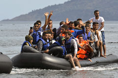 LESVOS, GRIECHENLAND am 12. Oktober 2015: Flüchtlinge, die in Griechenland im schmuddeligen Boot von der Türkei ankommen Stockbild