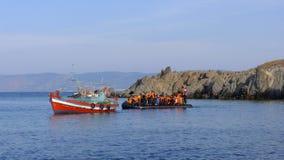 LESVOS, GRIECHENLAND am 18. Oktober 2015: Flüchtlinge, die in Griechenland im schmuddeligen Boot von der Türkei ankommen Stockfotografie