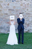 "Let's be crazy as ""Mrs. and Mr."". Newlywed couple acting funny, with white cartons of ""Mrs. and Mr."" covering their faces with royalty free stock image"