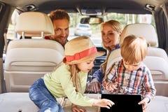 Let's vaga dove WiFi è debole Bambini svegli che giocano dentro l'automobile Viaggio stradale della famiglia fotografia stock