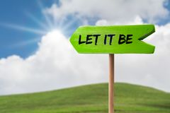 Let it be arrow sign. Let it be green wooden arrow sign on green land with clouds and sunshine royalty free stock image