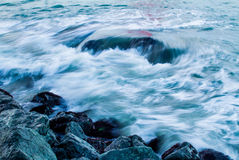 Ocean Waves On Rocks. The  incoming tide rushes over a submerged rock and crashes onto the rocky shore Stock Images