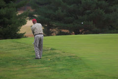 Let It Fly. Gentleman playing golf on beautiful fall day,ball in the air Royalty Free Stock Photos