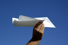 Let it fly. Child's hand about to through a paper plane royalty free stock image