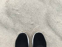 Let go. Black sport shoes on sand or beach with copy space. Concept let relax and exercise Stock Photography