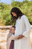 Let the little children come to me. Biblical scene when Jesus says, let the little children come to me, blessing a little girl. Historical reenactment at an old Stock Images