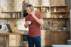 Attentive freelancer having telephone talk. Let me check. Cheerful man turning head to laptop while reading news and standing in the kitchen Royalty Free Stock Images