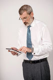 Let me check the stock update !. Senior entrepreneur browsing on his tablet pad Royalty Free Stock Photography