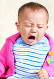 Let me down. Disappointed asian baby is crying Stock Photos