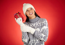Let me guess. Portrait of ecstatic girl in winterwear trying to guess what is in giftbox Royalty Free Stock Photos