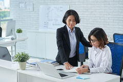 Let me help you. Experienced business lady helping her young coworker Stock Photo
