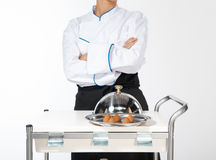 Let me introduce... Happy smiling caucasian female chef introducing new dish Stock Image