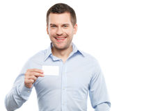Let me introduce myself with this business card. Waist up portrait of attractive young man presenting his visit card. He is standing and looking at camera Royalty Free Stock Photos