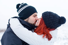 Let me kiss you, honey. Picture of a couple kissing on a winter background Stock Photos