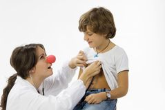 Let me know. Young and cute female doctor with a red nose visiting a little boy royalty free stock images