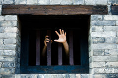 Let me out. Prisoner hands stretch out from prison bars stock photography