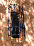 Let Me Out!. Window in red brick building covered by grate and black wrought iron royalty free stock photos