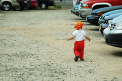 Let me pick up the car. Baby boy is walking in parking lot royalty free stock photo