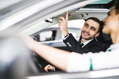 Let me show you interior of this car. Handsome young classic car salesman standing in the dealership and helping a client to make Stock Image