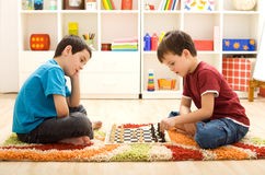 Let me show you a move - kids playing chess. Sitting on the floor in their room Stock Image