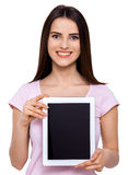 Let me show you something. Portrait of an attractive young woman showing a digital tablet screen to the camera isolated on white Royalty Free Stock Image