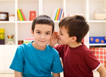 Let me tell you a secret. Boy whispering to his friend ear Stock Photo